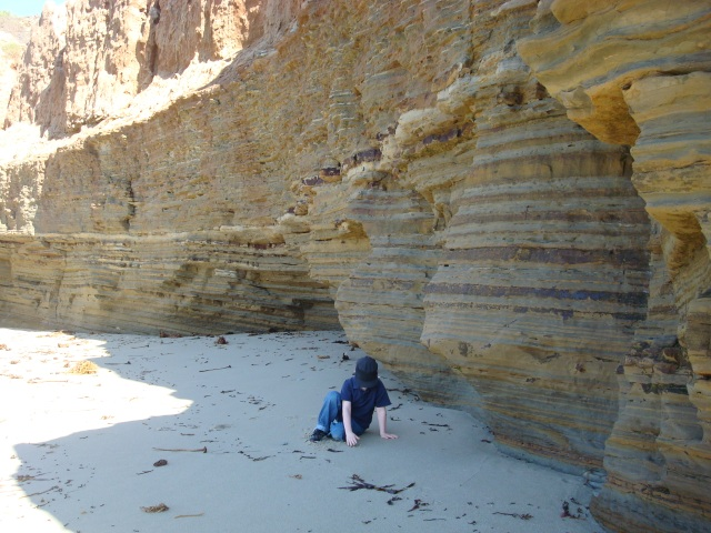 Boy by the sand cliffs
